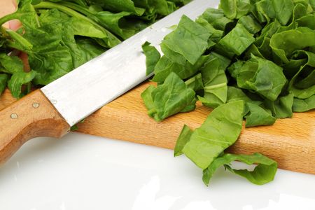 Chopped spinach and knife on wooden board isolated white background