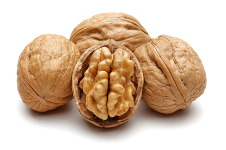 Whole and broken walnuts isolated on white background