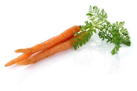 Verse wortelen met bladeren die op witte achtergrond worden geïsoleerd Stockfoto