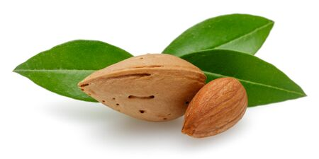 Almonds and green leaves isolated on white background