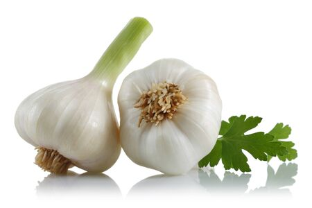 Fresh garlic bulbs with parsley leaves isolated on white background