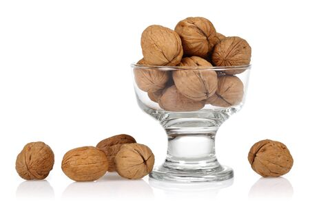 Whole walnuts in the glass bowl isolated on white background