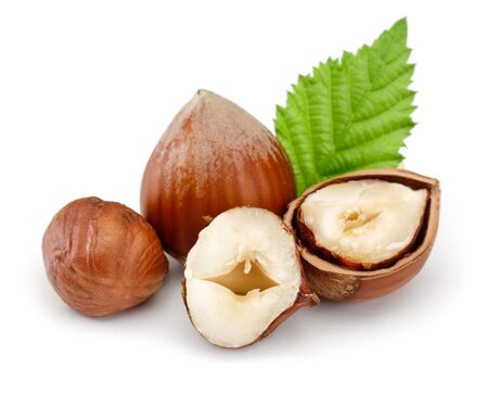 Group of hazelnuts with green leaves isolated on white background