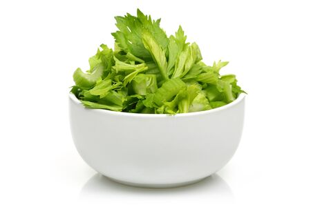 Fresh celery stalks chopped in a white bowl isolated on white background