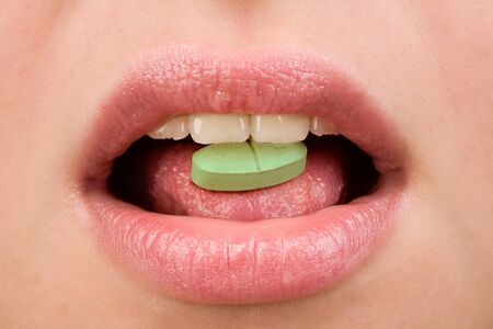 Closeup of woman taking green pill