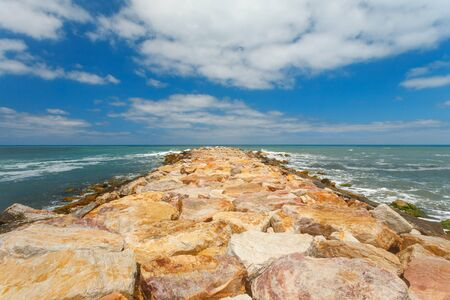 Rocks breakwater and white clouds in blue sky