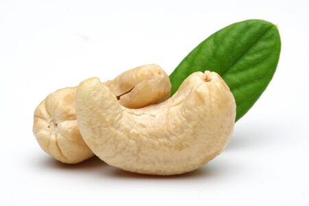 Raw cashew nuts with green leaf isolated on white background