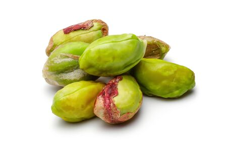 Heap of peeled pistachio nuts isolated on white background