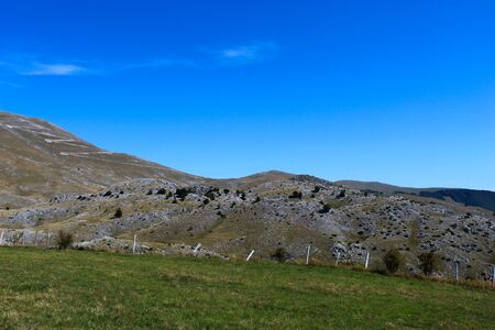 A meadow with a downed fence at the end of the meadow. In the background, mountain desolation, with little vegetation. On the way to the mountain Bjelasnica, Bosnia and Herzegovina.