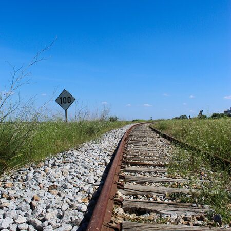 An old railway with a sign on the side that says 100. Railway in Beja, Portugal.