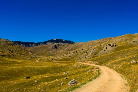 Oversaturated. Old mountain road, rocky landscape, mountain top in the background with blue sky and moon. Bjelasnica Mountain, Bosnia and Herzegovina.