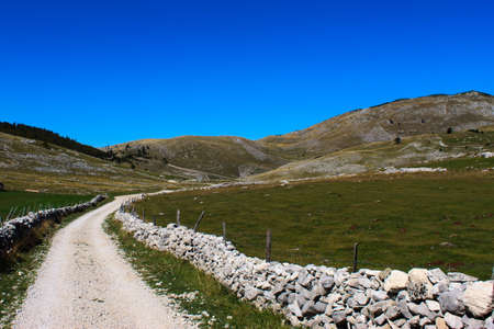 A mountain road surrounded by rocks. Mountain hills in the background. Bjelasnica Mountain, Bosnia and Herzegovina.