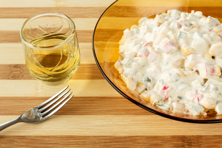 Traditional bulgarian appetizer - a glass of brandy type drink (grape rakia) and salad with pickles, corn, crab sticks and mayonnaise Reklamní fotografie