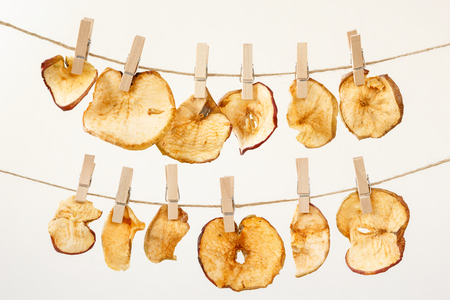Slices of dried apples hanging on a washing line tied with wooden clothespins on a light beige background. Drying fruits at home