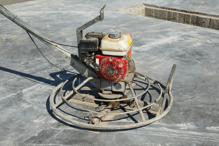 concrete surface finishing: Dirty power trowel machine on a brushed concrete surface Stock Photo