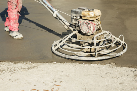 concrete surface finishing: Power troweling fresh concrete surface on a construction site. Power trowel concrete finishing machine working. Shallow depth of field