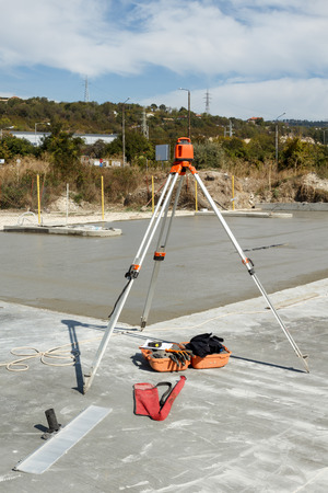 tripod mounted: Laser level mounted on a tripod for concrete slab leveling. Construction equipment on a building site