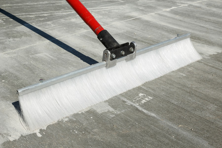 Close view of a concrete finishing broom with plastic bristles and red handle on a textured brushed finish