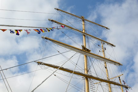 shrouds: Masts and rigging of a sailing ship with flags, against blue sky and clouds. Bottom-up view. Travel concept
