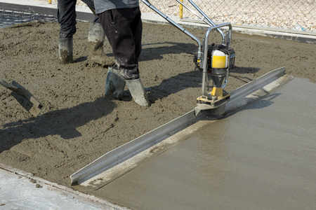 Smoothing fresh concrete with gas powered vibrating screed machine on a construction site Stock Photo