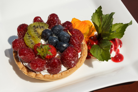 Tartlet with cheese cream, wild berries and kiwi, on a white plate, decorated with orange flower, leafs, cream and jam, served on a wooden table