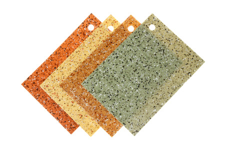 Four samples of colored rubber flooring, isolated on white background.