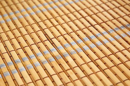 Close up of a bamboo table mat with colorful thread. Selective focus and shallow depth of field Stock Photo