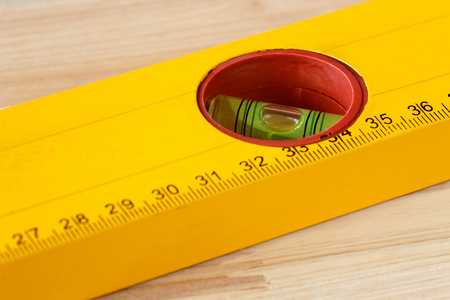 Extreme close up of a yellow ruler with a bubble level on a wooden background. Shallow depth of field, focus on the spirit