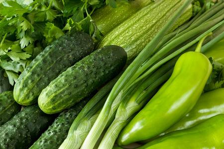 Fresh, organic green vegetables background. Cucumber, green pepper, parsley, zucchini, scallions