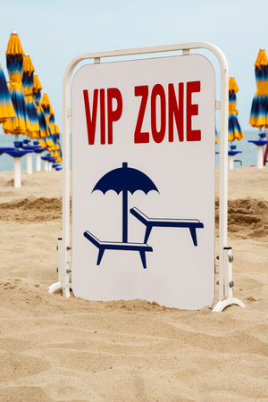 VIP Zone sign in the sand with beach lounge chairs and sunshade
