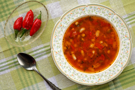 Homemade delicious traditional bulgarian bean soup (bob chorba) served with red chili peppers