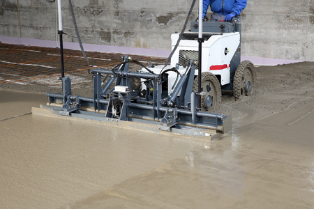 Laser screed machine leveling fresh poured concrete surface on a construction site