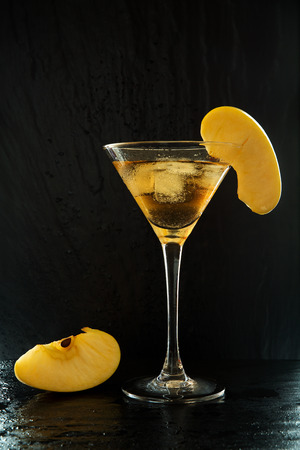 Fresh summer appletini cocktail in a martini glass with an apple slices on a black, wet textured surface with water drops and reflections