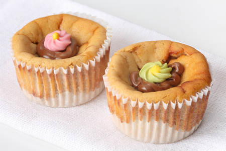 Close up of two delicious small cheesecakes with melted chocolate and colorful sugar flowers icing Banco de Imagens