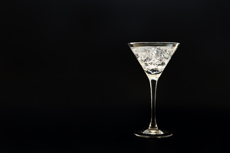 Cocktail with crystal like crushed ice in a martini glass outlined with back light against black background. Space for text