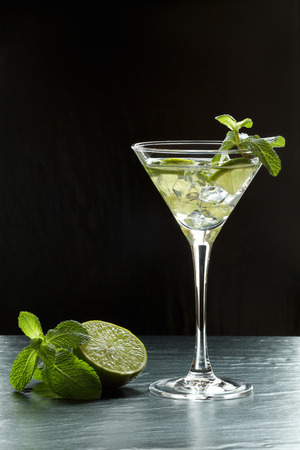 Summer fresh cocktail with lime slices, crushed ice and mint leaves in a martini glass backlit on black background