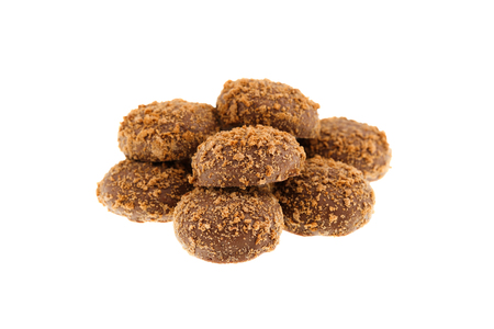 Close up of a pile of delicious crunchy caramel biscuits coated with milk chocolate and biscuit particles, isolated on a white background