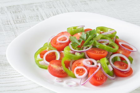 Healthy, fresh and delicious vegetable salad with cherry tomatoes, red onion rings, green pepper rings, parsley and olive oil