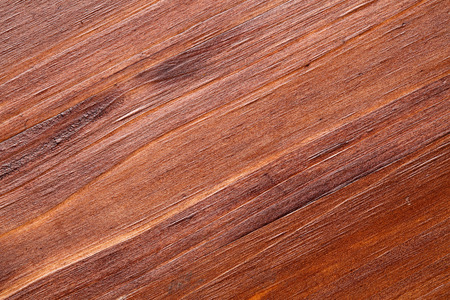 Extreme close up of a pine wooden surface, finished with dark wood stain, patina and matte varnish