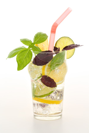 Fresh summer fizzy cooler cocktail with lemon and limette wheels, ice cubes and red and green basil leaves with a straw on a lighted background