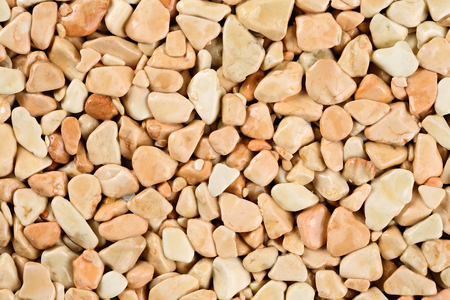 Extreme close up natural stone carpet, beige and cream coloured in different shades and tints of beige. Decorative stone coating. Slip resistant floor finish containing natural stone particles.
