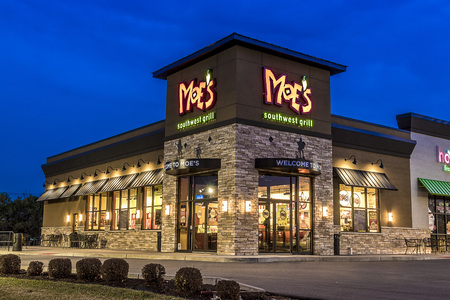 Utica, NY - DECEMBER 02, 2017: A Moe's Southwest Grill Restaurant Illuminated at Night. Moe's is A Fast Casual Dining Mexican Food Restaurant with over 680 Locations in 40 States As of 2016 And New Branches Have Opened Oversees Now. Editorial