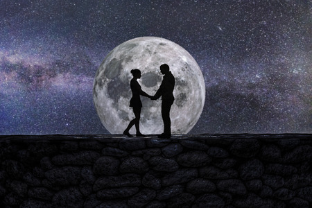 Silhouette of Two Lovers Standing on A Huge Fence in The Night, Giant Moon and Milky way in The Background