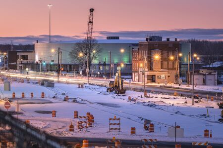 Utica, New York - Jan 20, 2020: Night View of a Work Zone in the Foreground and Adirondack Bank Center at the Utica Memorial Auditorium in the Background.