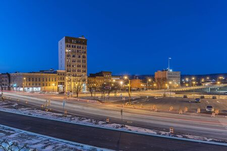 UTICA, NY - JAN 17, 2020: Wide Aerial Night View of Downtown Utica Streets and Cars Trail Lights with the Genesee Tower in the Background.