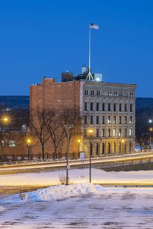 UTICA, NY - JAN 20, 2020: Closeup Aerial Night View of Downtown Utica Streets and Cars Trail Lights with Commercial Travelers Life Insurance Company Building in the Background.