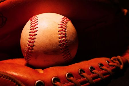 catcher's mitt: A lightpainted photo of a baseball sitting in catchers mitt