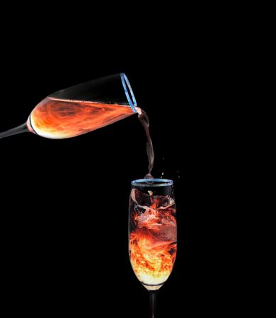 Glass of orange neon liquid pouring into another