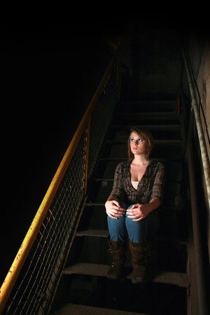 A young woman sitting in shadows photo