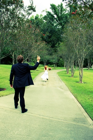 Cross processed photo of a bride running away from her groom photo